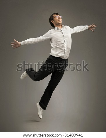 Studio shot of a jumping happy businessman - stock photo