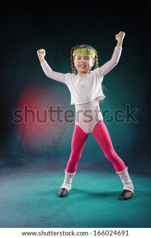 studio shot of a little girl at fitness exercise