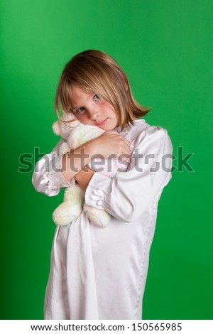 Studio shot of a little girl in a nightgown holding a teddy bear on green background