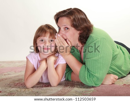 Studio shot of a little girl lying on a carpet being embraced by her mom telling secrets
