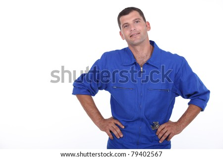 Studio shot of a man in blue overalls with his hands on his hips - stock photo