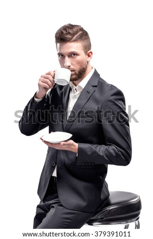 Studio shot of a man wearing black suit and white shirt with open collar holding, drinking from white cup, isolated on white, sitting on bar stool - stock photo