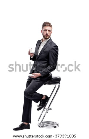 Studio shot of a man wearing black suit and white shirt with open collar holding white cup, isolated on white, sitting on the bar stool - stock photo