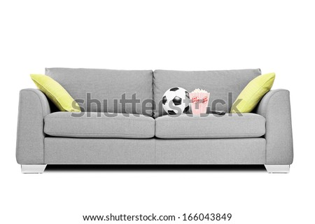 Studio shot of a modern couch with soccer ball and popcorn box on it isolated on white background - stock photo