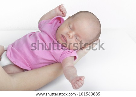 Studio shot of a moth holding newborn baby girl over the changing table. - stock photo