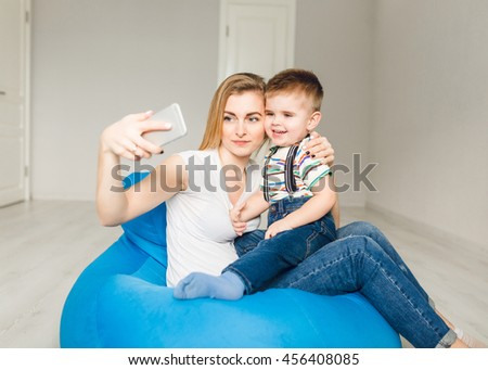 Studio shot of a mother holding her child and taking a selfie on smartphone. Mom wears white t-shirt and jeans, and boy is dressed into jeans and white shirt. They sit on blue sack chairs. - stock photo