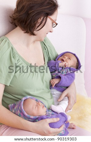 studio-shot of  a mother holding her identical ( similar ) twin baby girls in her arms. twins wearing handmade knitted  cardigans. - stock photo