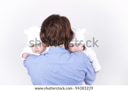 studio-shot of a mother holding her identical twin baby daughters over the shoulder, on a white background. - stock photo