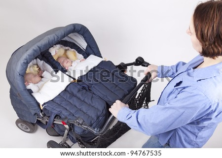 studio-shot of a mother pushing a baby buggy with her identical twin daughters, on a white background.