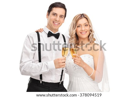 Studio shot of a newlywed couple holding glasses of white wine and posing together isolated on white background - stock photo