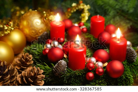 Studio shot of a nice advent wreath with baubles and three burning red candles - stock photo