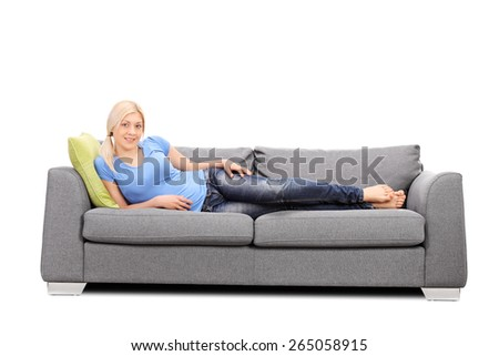 Studio shot of a pretty blond woman lying on a modern gray sofa isolated on white background - stock photo