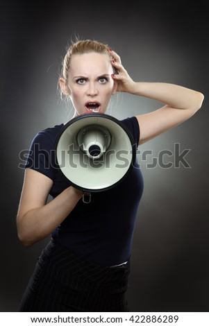 Studio shot of a pretty business model shouting into a megaphone.  Shot on a grey background.