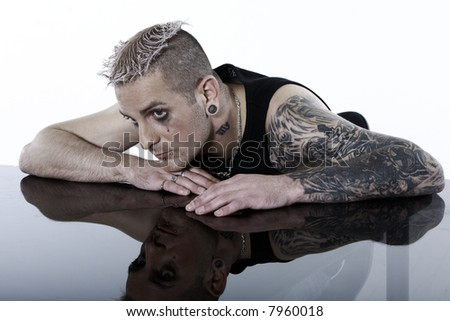 studio shot of a sad romantic  man  with tatoos and piercing - stock photo
