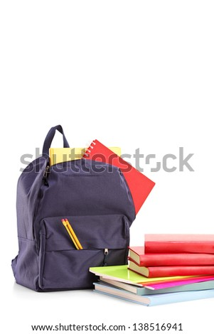 Studio shot of a school backpack with books and notebooks, isolated on white background - stock photo