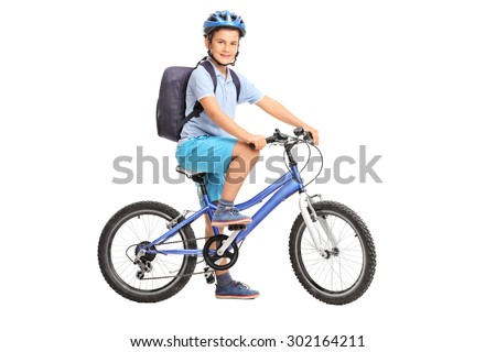 Studio shot of a schoolboy riding a bicycle and looking at the camera isolated on white background - stock photo