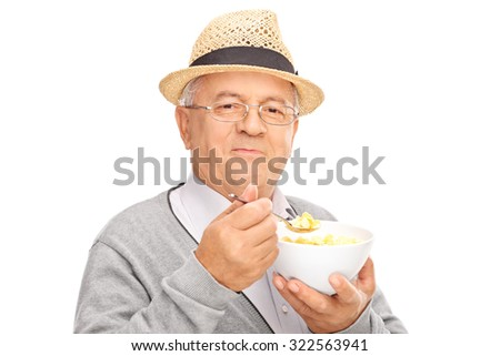 Studio shot of a senior gentleman eating cereal from a bowl and looking at the camera isolated on white background - stock photo