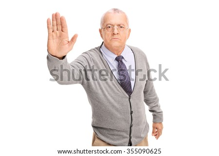 Studio shot of a senior gentleman making a stop gesture with his hand and looking at the camera isolated on white background - stock photo