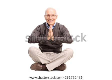 Studio shot of a senior gentleman meditating seated on the floor isolated on white background