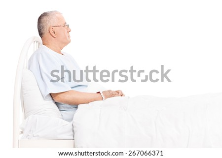 Studio shot of a senior patient in a hospital gown, lying in a bed and looking around isolated on white background - stock photo