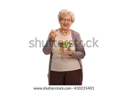 Studio shot of a senior woman eating a salad and looking at the camera isolated on white background - stock photo