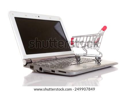Studio shot of a  shopping cart over a laptop computer - stock photo