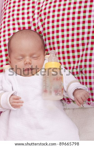 studio-shot of a sleeping newborn baby girl after drinking milk from a bottle. - stock photo