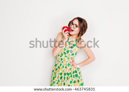 Studio shot of a smiling brunette girl smiling widely. Girl wears black glasses and yellow and green dress. She holds a red apple in her right hand and is about to bite it.