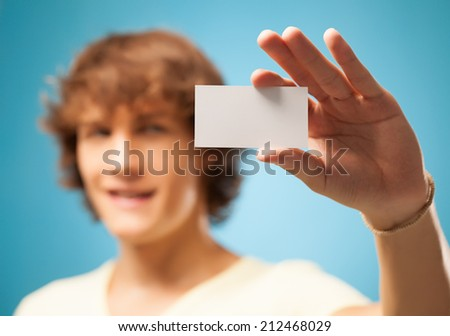 Studio shot of a smiling young man holding out a blank business card.
