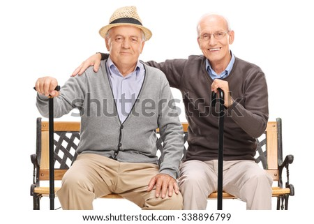 Studio shot of a two old friends posing together seated on a wooden bench isolated on white background - stock photo