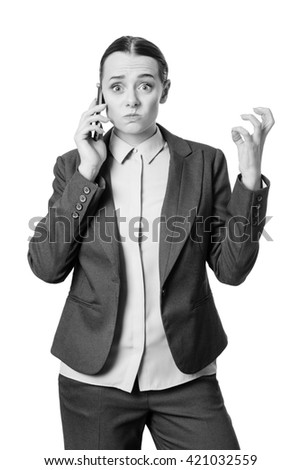 Studio shot of a worried and frustrated looking business woman, who is talking on the phone, using her hand to gesture.   - stock photo