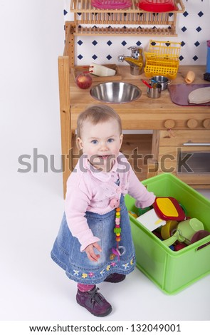 studio shot of a 1 year old baby girl playing in a selfmade wooden kitchen. - stock photo