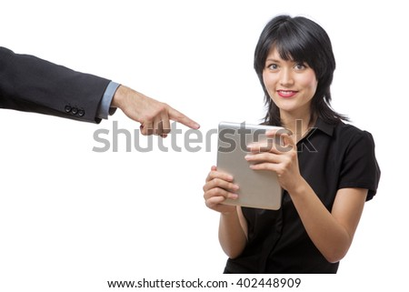 Studio shot of a young beautiful happy business woman using tablet computer with a male collegues arm in a suit coming into the shot pointing to the computer - stock photo
