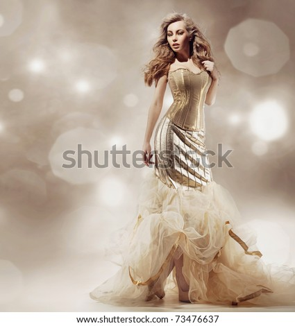 Studio shot of a young beauty wearing luxury dress - stock photo