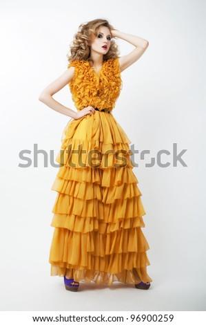 Studio shot of a young beauty woman wearing fashion luxury yellow bright dress - stock photo