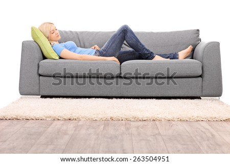 Studio shot of a young blond woman taking a nap on a sofa isolated on white background - stock photo