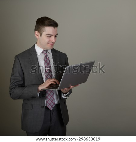 Studio shot of a young business man in a suite posing in the studio on a light grey background with a stylish haircut holding a laptop - stock photo