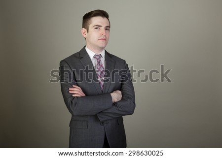 Studio shot of a young business man in a suite posing in the studio on a light grey background with a stylish haircut and arms folded looking confident - stock photo