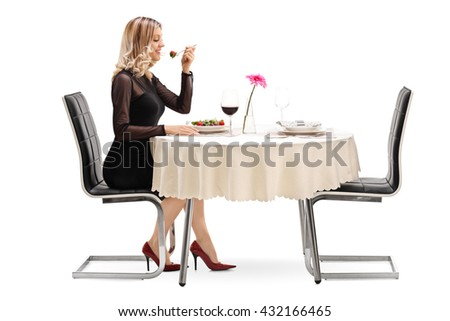 Studio shot of a young cheerful woman eating a salad seated at a restaurant table isolated on white background - stock photo
