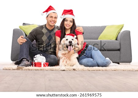 Studio shot of a young couple and their dog wearing Santa hats and celebrating Christmas seated on the floor next to a modern sofa isolated on white background  - stock photo