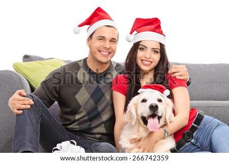 Studio shot of a young couple and their dog wearing Santa hats and celebrating Christmas seated on the floor next to a modern grey sofa isolated on white background - stock photo