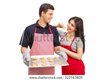 Studio shot of a young couple holding an aluminum pan with chocolate chip cookies isolated on white background - stock photo