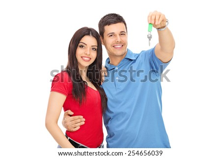 Studio shot of a young couple posing with a key isolated on white background - stock photo