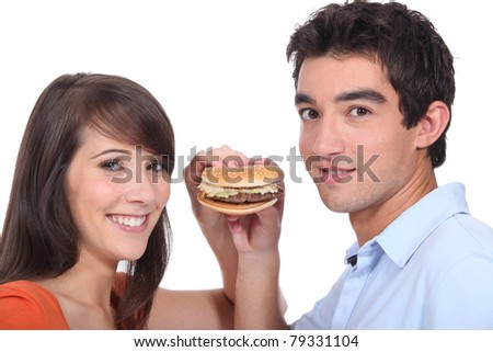Studio shot of a young couple sharing a hamburger - stock photo