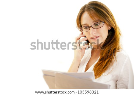 Studio shot of a young executive holding papers and talking on the phone - stock photo