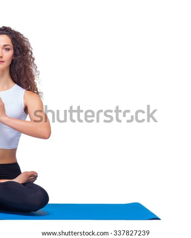 Studio shot of a young fit woman doing yoga exercises on white background - stock photo
