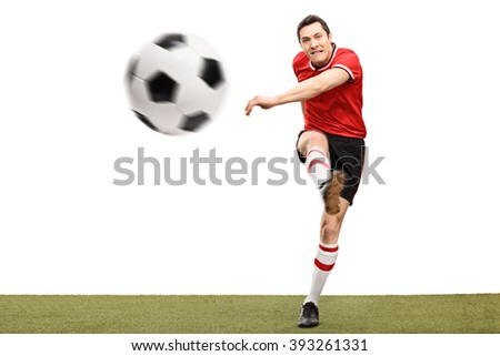 Studio shot of a young football player kicking a ball on a grass surface isolated on white background - stock photo