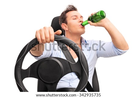 Studio shot of a young irresponsible driver driving and drinking a beer isolated on white background - stock photo