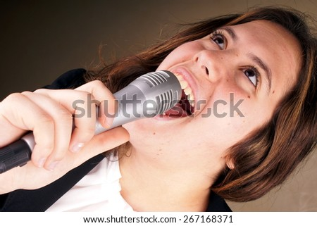 Studio shot of a young lady with microphone