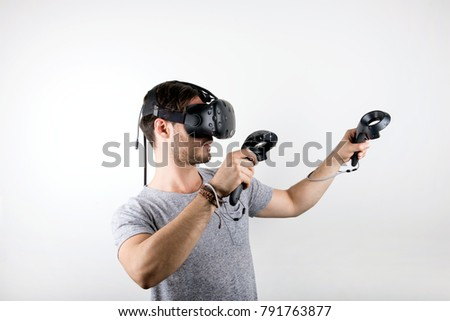 studio shot of a young, male model looking through virtual reality (VR) headset with handheld controllers., immersed into his experience. isolated on white background.